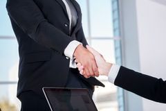 Meeting business partners. Two businessman shaking hands with ea Stock Photography