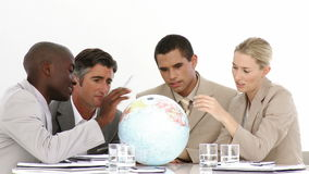 A meeting of business people around a terrestrial globe Royalty Free Stock Photo