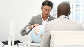 A meeting of businessmen around a terrestrial globe. Against a white background stock video footage