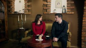 Meeting in a cafe. Boy and girl in pleasant company over coffee in a small cafe stock video footage