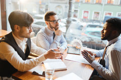 Meeting in cafe. Three young men having start-up meeting in cafe royalty free stock image