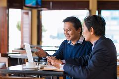 Meeting in cafe. Two Asian businessmen having meeting in the cafe Stock Photos