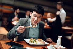 Meeting with chinese businessmen in restaurant. Man is eating sushi. stock photography