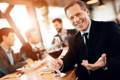 A man in a suit with a glass of wine in his hand. Adult men sitting at a table in a restaurant looking at the camera and holding wine in his hands. A men in a