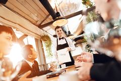 Meeting with chinese businessmen in restaurant. Men are choosing wine. stock image