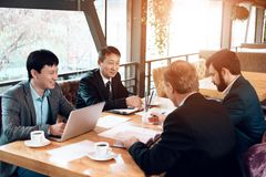 Meeting with chinese businessmen in restaurant. They are sitting behind table. Meeting with chinese businessmen in suits in restaurant. They are sitting behind stock photography