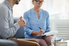 Meeting counselor. Man with hand in hand listening to counselor at session while sitting on couch next to her stock images