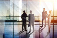 Meeting and crowd concept. Businesspeople silhouettes in abstract glass office interior. Meeting and crowd concept. Double exposure royalty free stock images