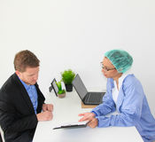 Meeting between a doctor and a patient in at the office with forms Stock Photos