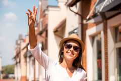 Meeting friend. Beautiful young woman in hat and sunglasses waving to someone and smiling while standing outdoors Royalty Free Stock Photo