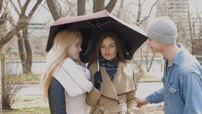 Meeting friends in the park. Two blonde girls and a brunette stand under an umbrella when it rains. A young man stock video footage