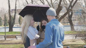 Meeting friends in the park. Two blonde girls and a brunette stand under an umbrella when it rains. A young man stock footage