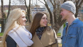 Meeting friends in the park. Two girls blonde and brunette stand and talk. A young man approaches them. They cheerfully. Say hello and talk. The sun is shining stock video footage