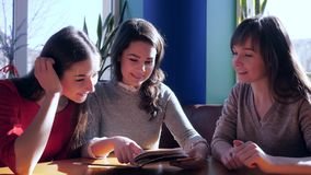 Meeting of girlfriends in restaurant, smiling girls watching menu sitting at table. Indoors stock footage