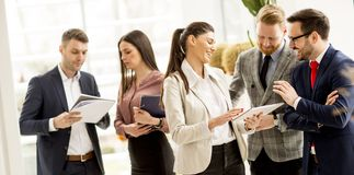 Meeting of group of businesspeople in the office standing in fro. Nt of  large window in modern office stock images