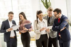 Meeting of group of businesspeople in the office standing in fro. Nt of  large window in modern office royalty free stock photo