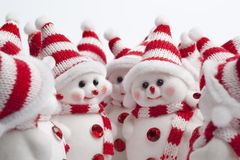 Meeting of a group of little snowmen. With white and red hats Royalty Free Stock Photo
