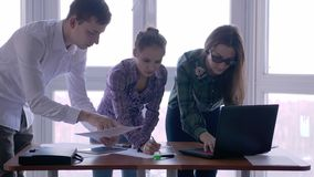 Meeting of group people at the working place in a stylish office with large panoramic window. Looking on screen pc and stock video