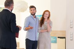 Meeting with house consultant. Young couple looking at interior of house for sale at a meeting with consultant stock photography