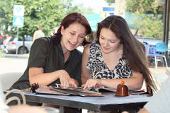 Meeting at lunch. Two young women laughing review magazine  in a small cafe Royalty Free Stock Images