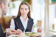 Meeting by lunch. Serious young businesswoman sitting by table in restaurant by lunch and listening to her colleague explanation Royalty Free Stock Images