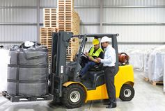 Meeting of the manager and worker in the warehouse - forklift an. D interior of the industrial building stock photos