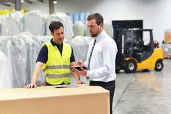 Meeting of the manager and worker in the warehouse - forklift an. D interior of the industrial building Royalty Free Stock Photo