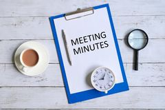 Meeting minutes written on a clipboard. Top view of clipboard with paper written `MINUTES MEETING` with magnifying glass, pen, table clock and a cup of coffee royalty free stock photos