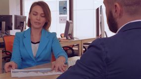 Meeting in modern office. Adult professional business woman explain about income growth. attractive caucasian worker looking on tables and diagrams talking with stock video footage
