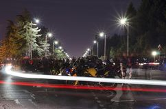 Meeting of motorcycle drivers. Race with many noise and smoke. Meeting is during the begining of night. Street is lighted by street lighting. Regular traffic royalty free stock image