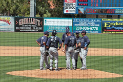 A meeting on the Mound as Seen from Behind the Backstop Stock Images