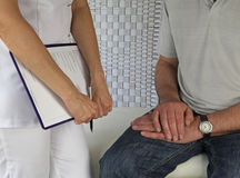 Meeting a new client. Female massage therapist standing beside seated male client, holding clipboard Royalty Free Stock Photos