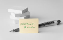 Meeting note. Meeting reminder on a post-it note and a ballpoint in grey scale Royalty Free Stock Image