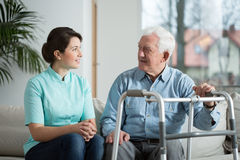 Meeting with nurse. Elderly sick men meeting with his young pretty nurse Royalty Free Stock Image