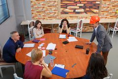 Meeting at the office. At the round table the team sits, and next to it there is a chief in a helmet. royalty free stock image