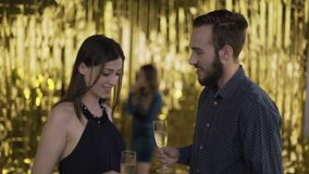 Meeting at a party. Man and woman meet at the disco. Close-up on a gold background. 4k. Meeting at a party. Man and woman meet at the disco. Close-up on a gold stock video footage