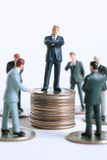 Meeting point. Business man on coin stack with his team stock images