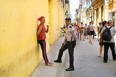 A meeting with a policeman. Cuba, Havana - 07 April, 2016: a busy street of Havana - a viaduct for tourists who are passing by day and night, a local woman Royalty Free Stock Images