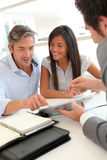 Meeting in real-estate agency. Real-estate agent showing house plans on electronic tablet Stock Photo