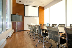 Meeting Room. Empty Meeting Room with desk and chairs in raw and screen on the wall Stock Photo