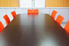 Meeting room. With brown table , orange armchairs and wood wall Royalty Free Stock Photography