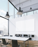 Meeting room with blank poster. Meeting room for six, blank poster on wall, lamps above. Panoramic window, city view, natural light. Loft. Concept of meeting. 3D Royalty Free Stock Photos