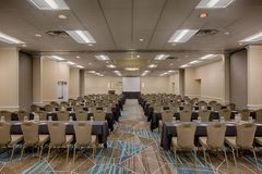 Meeting Room Event Hall. This is a big huge room used for meetings and events. Most likely business convention with tables and chairs and a projection screen royalty free stock image