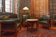 Cosy VIP meeting room. Luxury old meeting room inside a castle with armchair and round table on a carpet for very important person royalty free stock photos