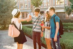 Meeting smiling friends teenagers in the city, happy young people greeting each other, hugging giving high five. Friendship and royalty free stock image
