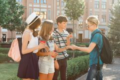 Meeting smiling friends teenagers in the city, happy young people greeting each other, hugging giving high five. Friendship and stock photos