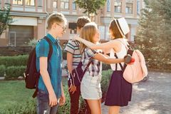 Meeting smiling friends teenagers in the city, happy young people greeting each other, hugging giving high five. Friendship and stock images