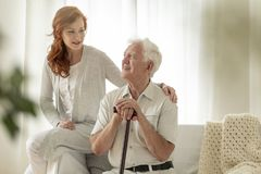 Meeting of smiling granddaughter with happy grandfather with walking stick at home. Concept stock photos