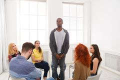 Meeting of support group, therapy session. African american men patient standing in circle and telling his problems to therapy group, copy space royalty free stock photography