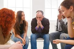 Meeting of support group, therapy session. Meeting of support group. Depressed men sitting at rehab group therapy. Psychotherapy, depression, life issues concept stock image